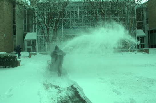 A worker clears the sidewalk with a snowblower, Old Dominion University